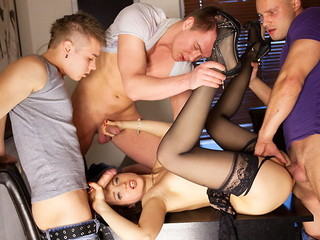 Lewd lingerie doll in black stockings Taissia gets discharged on hardcore porno movie scene when drilled by three dudes